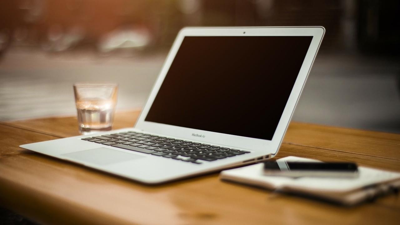 Dator, vattenglas, block och en mobil.