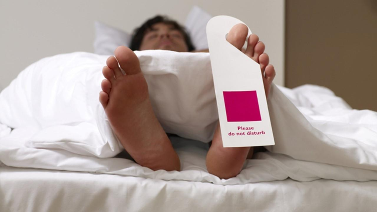 tired man in bed wanting to get more sleep with do not disturb sign hanging on toe