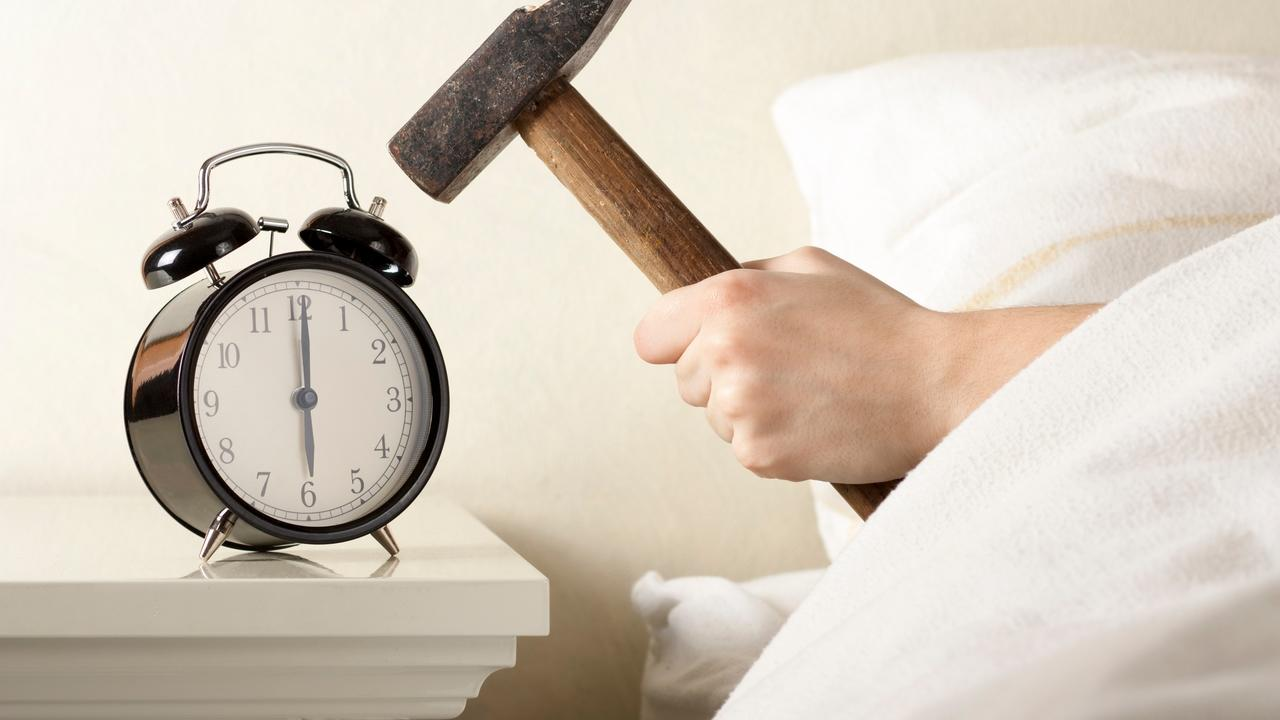 person not getting enough uninterrupted sleep bangs alarm clock with hammer