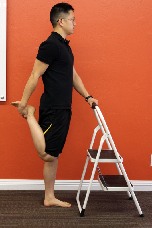 Matt Hsu demonstrates a quad stretch with the support of a chair.
