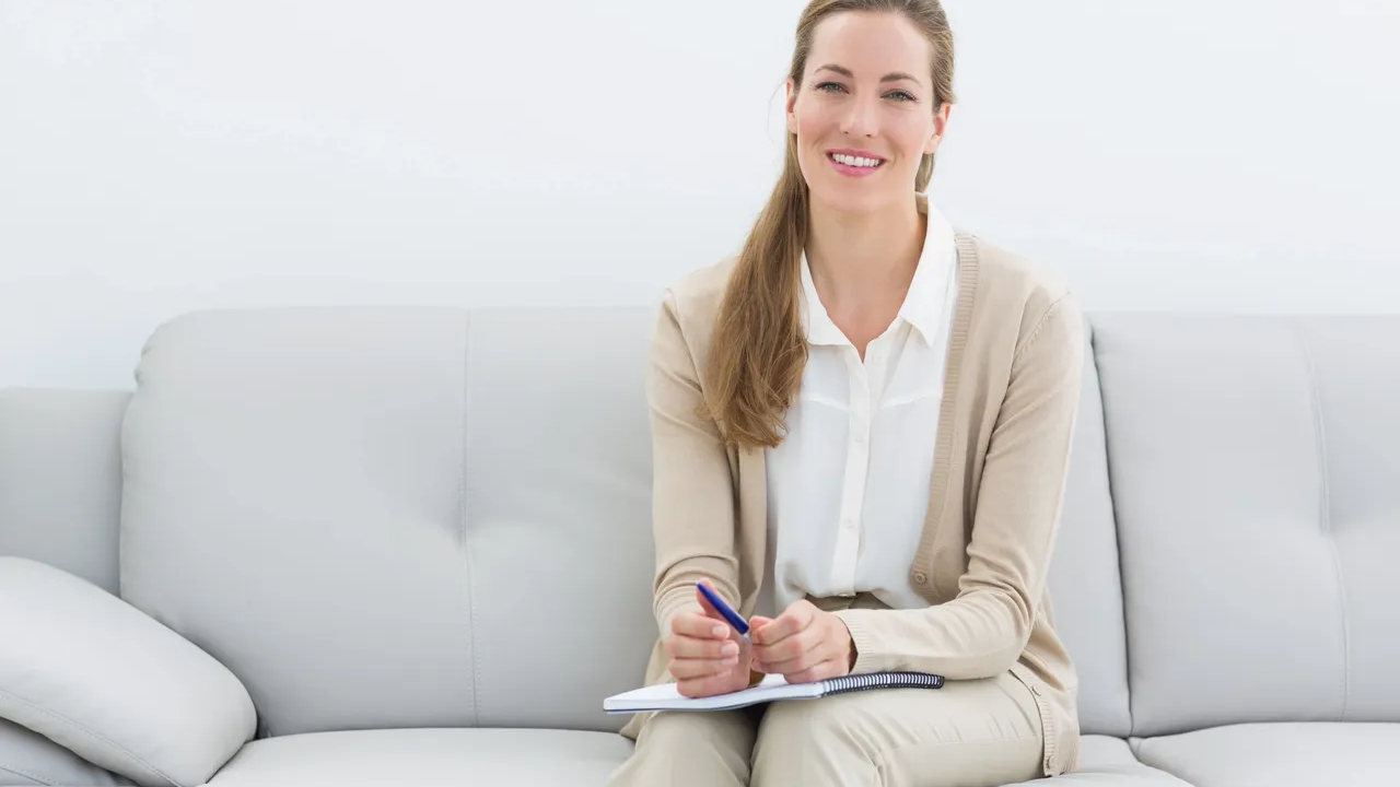 Woman sitting on a white sofa with a notepad in her hand wearing a light brown cardigan and khaki pants