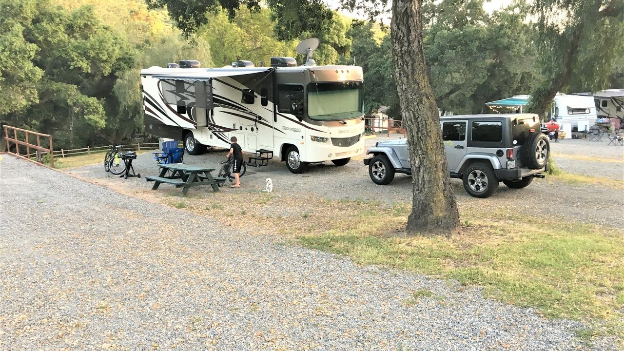 Picture of RV with Jeep Wrangler in front of it.