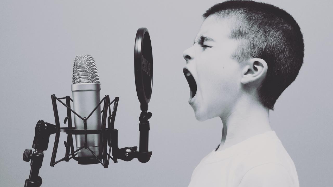 Child screaming into retro microphone.