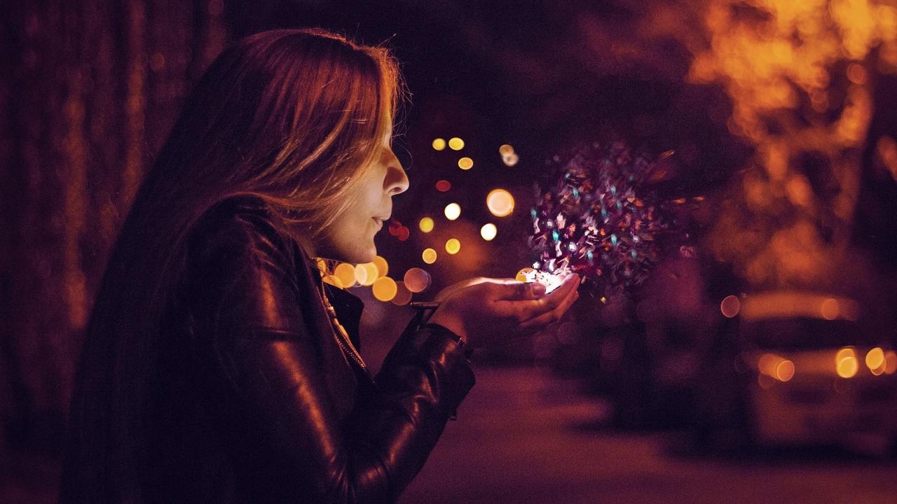 Woman blowing fairy dust.
