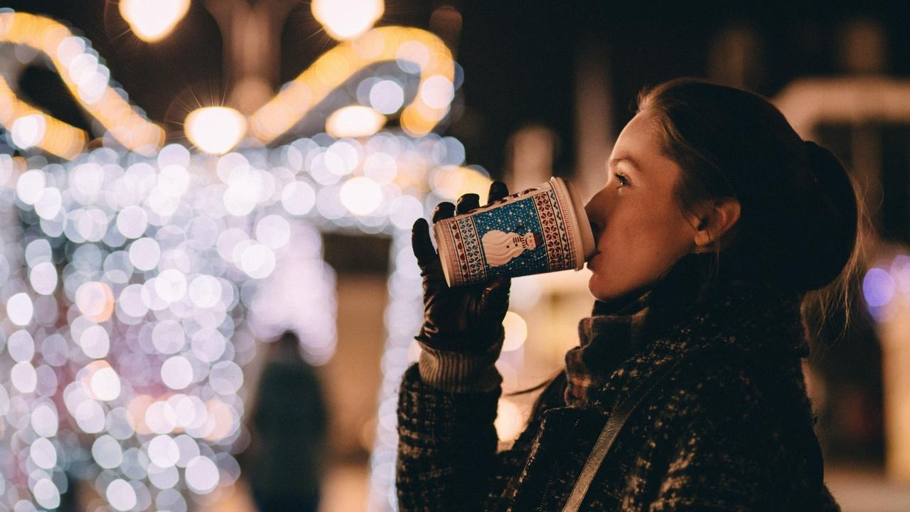 Woman drinking hot drink with holiday lights in background.