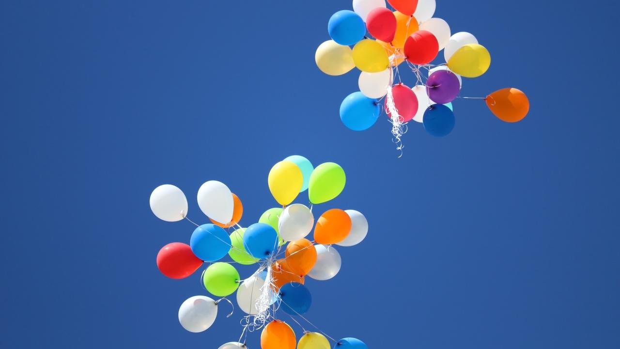 Clear blue sky with a bunch of balloons floating away.