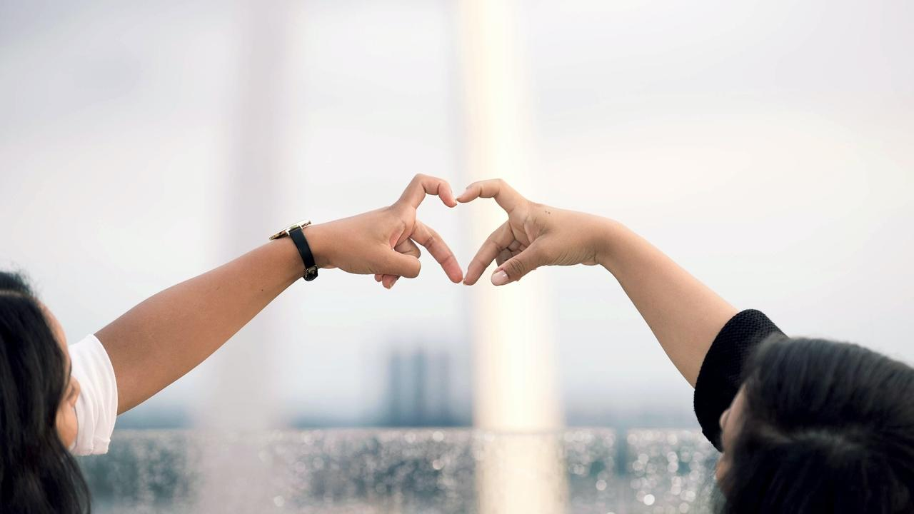 Two people creating a heart symbol with fingers in front of St. Louis Arch