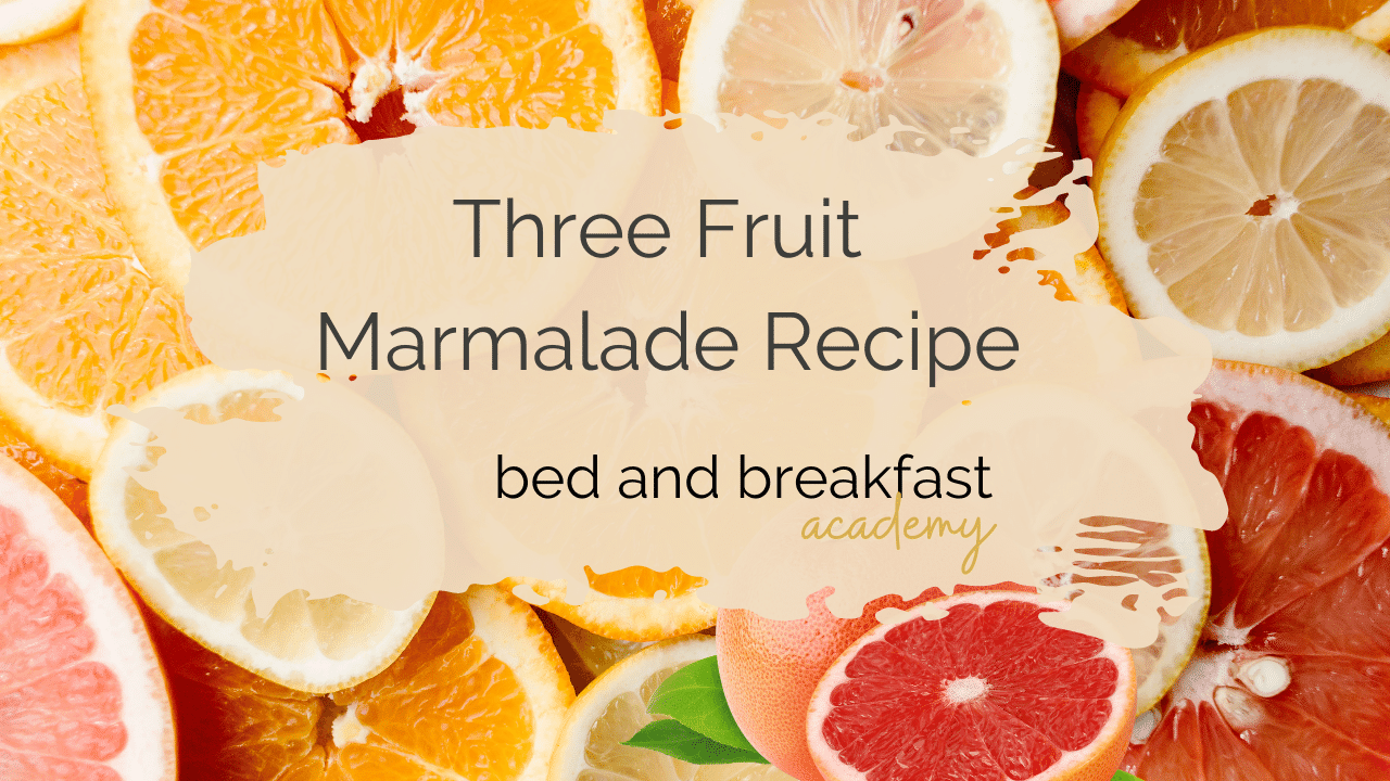 Slices of orange, pink grapefruit and lemon with the words three fruit marmalade recipe