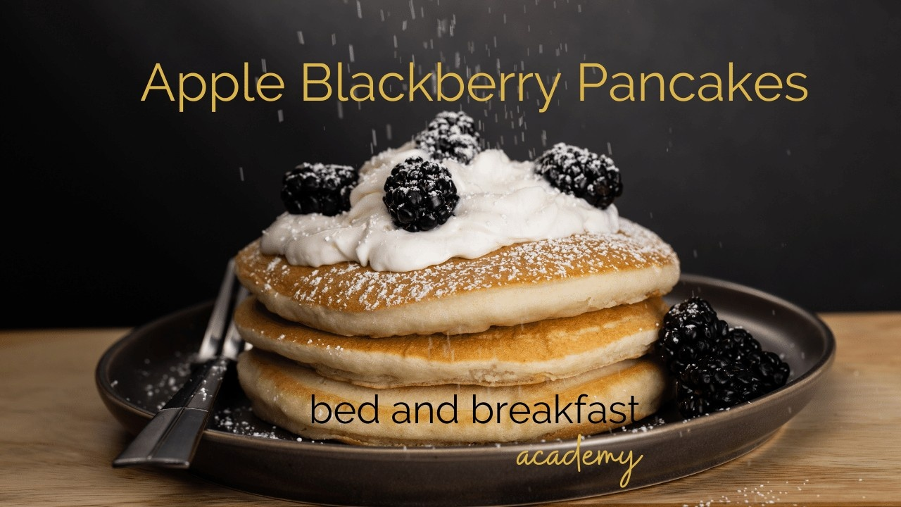 Blackberry Pancakes on a brown plate topped with cream and blackberries