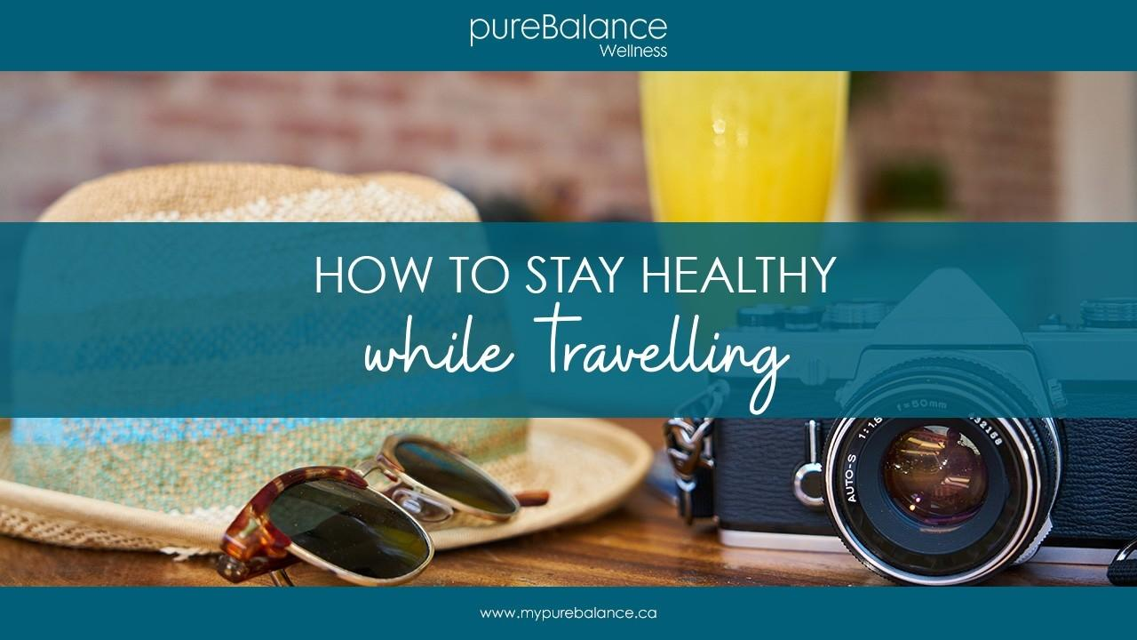 camera, sunglasses and hat on cafe table - How To Stay Healthy While Travelling - Article by pureBalance Wellness Cancer Care