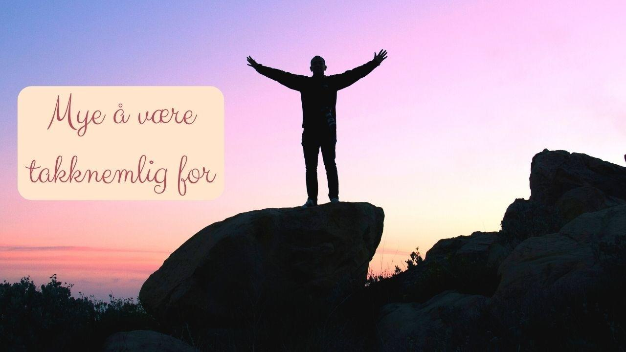 Viktigheten av takknemlighet. Mye å være takknemlig for. En person står på en sten med hendene i været og feirer på en måte. Himmelen er farget i rosa, blått og korall og landskapet og personen er i siluett.