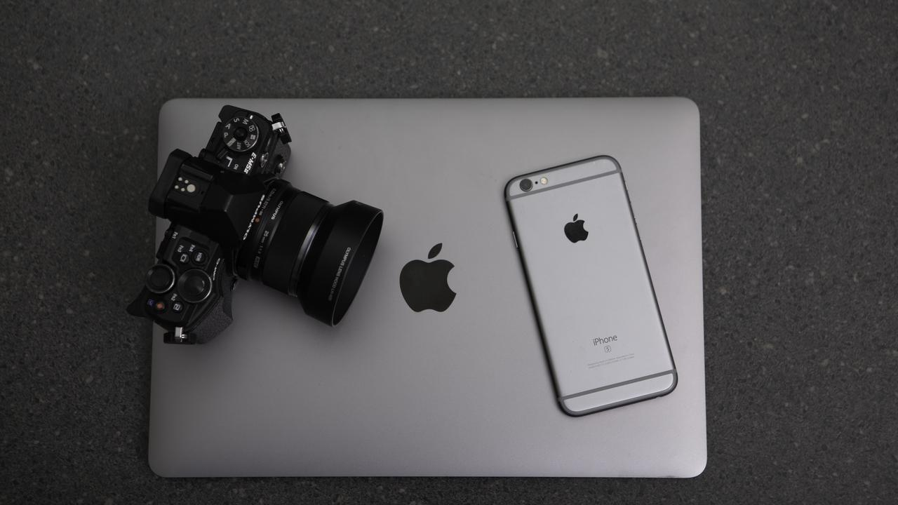 camera and an iphone sitting on a laptop