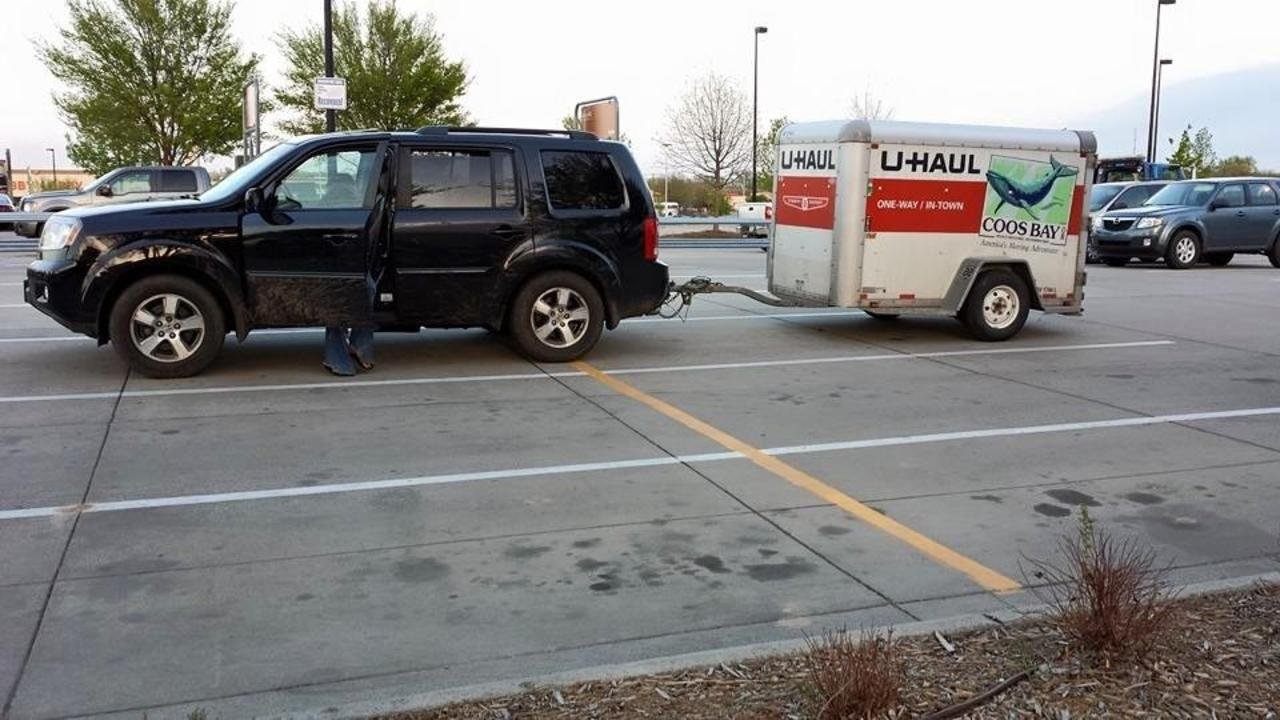 car and uhaul trailer in a parking lot