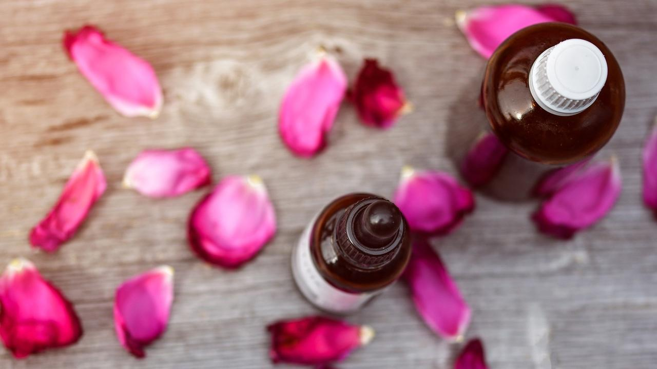 essential oil bottle with rose petals