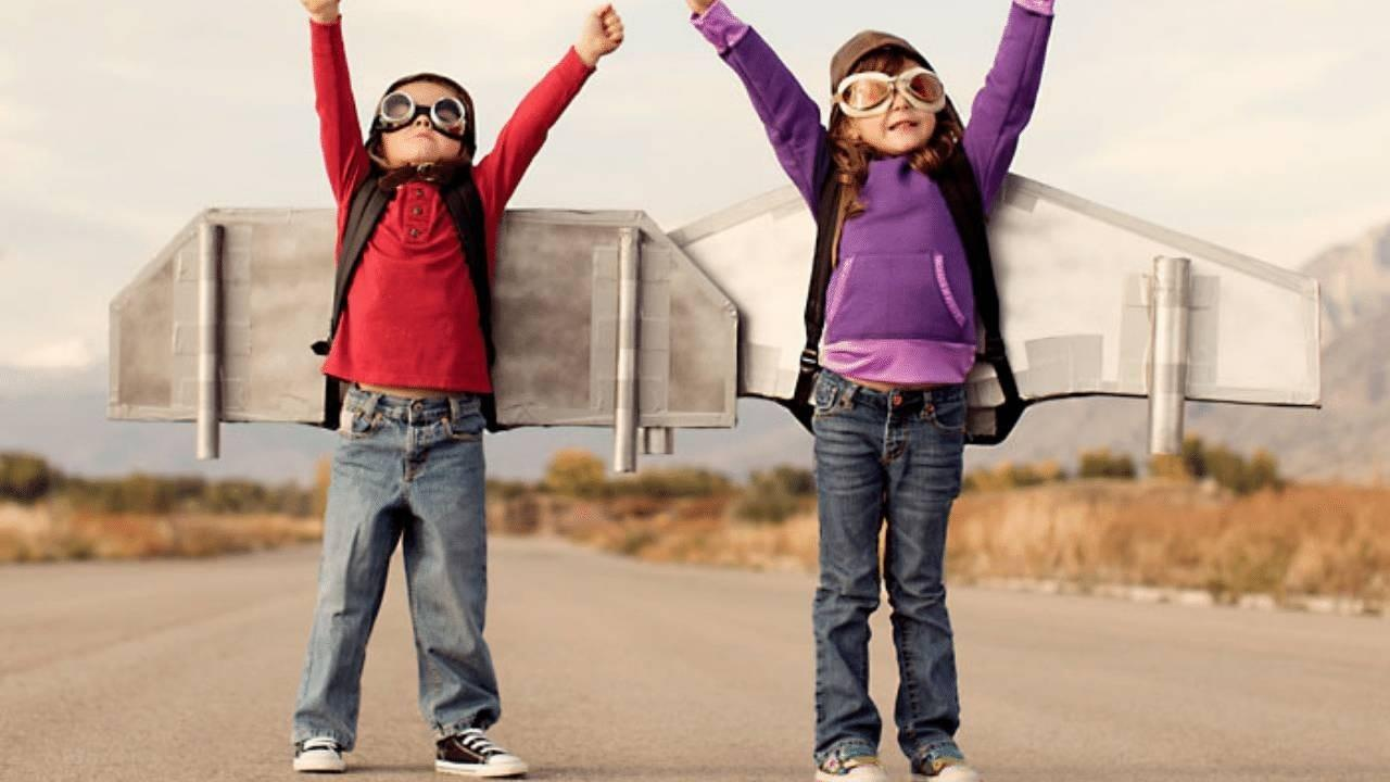 Two children dressed as pilots with goggles and plane wings attached to their backs stand on a wide road on an empty field with their arms raised up high