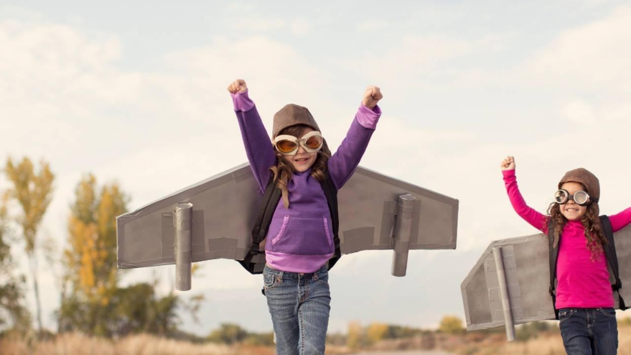 A child wearing a purple sweater with plane wings strapped to her back runs enthusiastically towards the camera