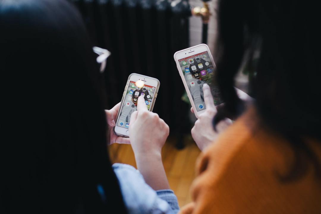 dos personas en sus Teléfonos con Telegram para negocios