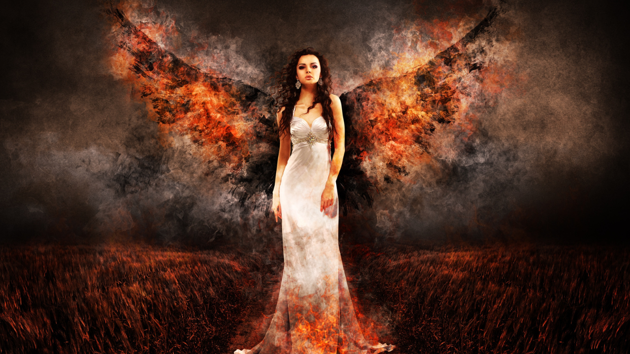 Angel woman stands in the fire with fire on her wings as she looks fierce - representing the phoenix rising and a woman in her power and truth as she rises from the ashes