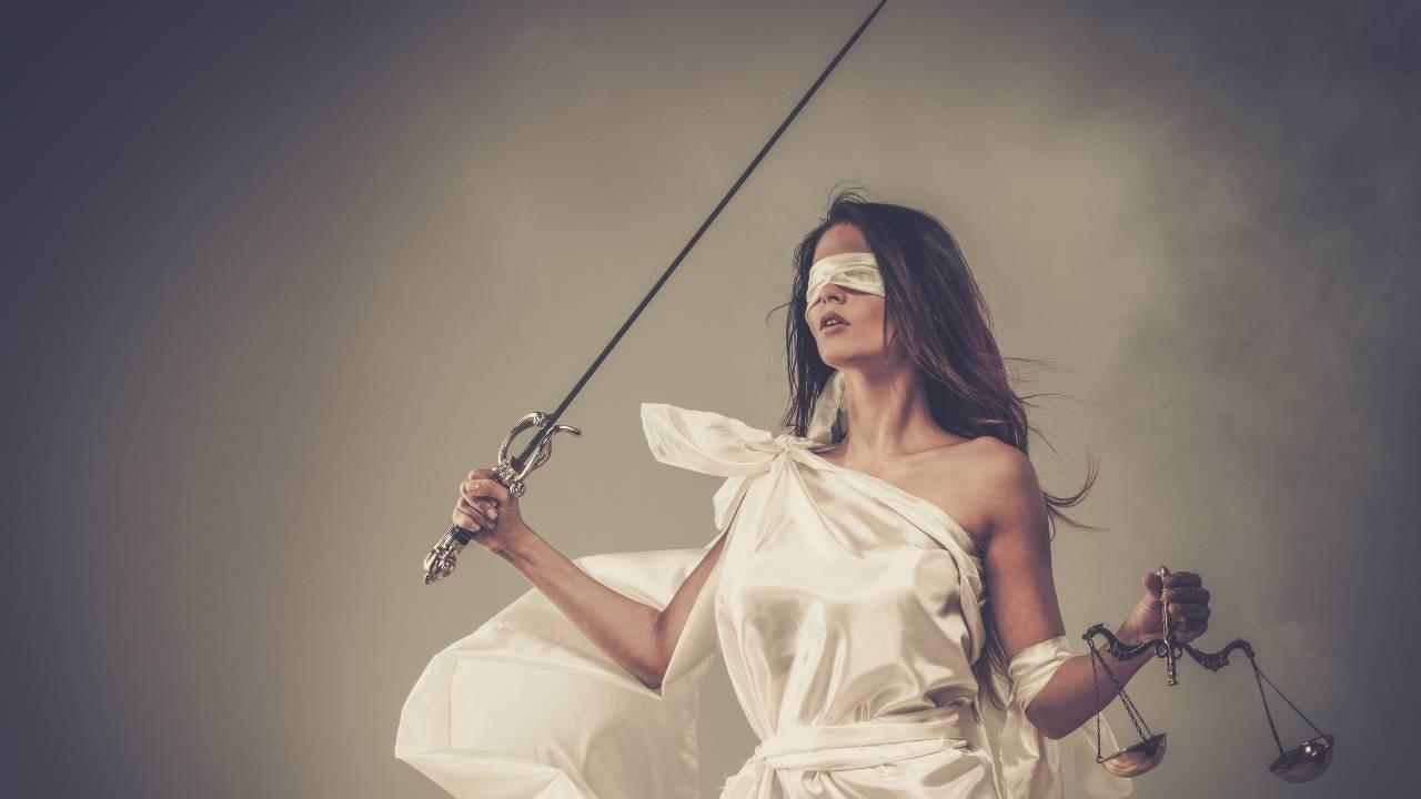 Blindfolded Lady Justice holds the scales and swords to represent truth