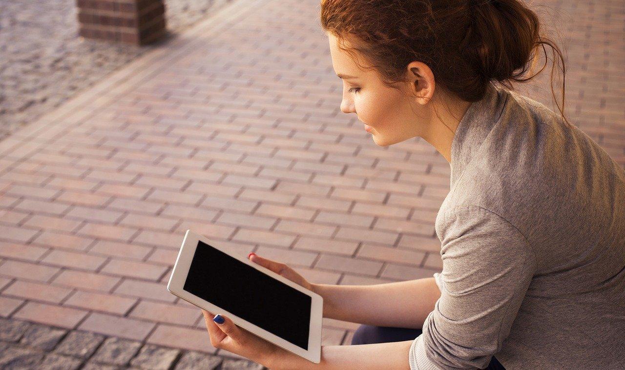 woman looking at ipad near walkway