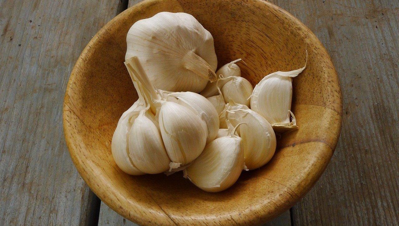 garlic cloves in wooden bowl