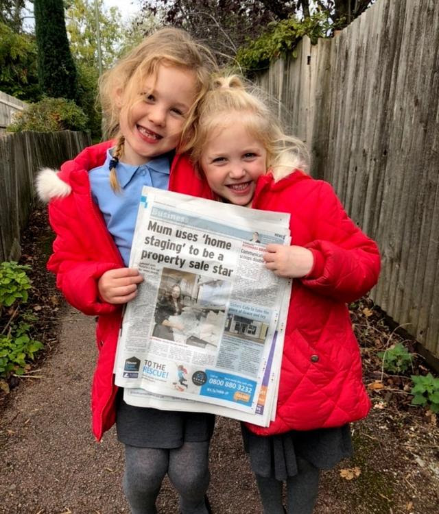 two kids holding up a newspaper