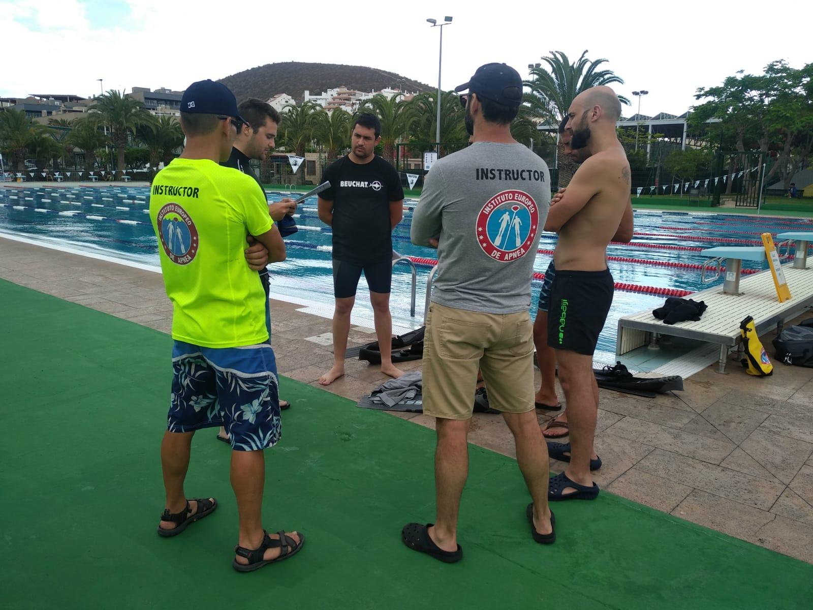 Grupo de instructores de apnea haciendo un briefing de la clase de buceo