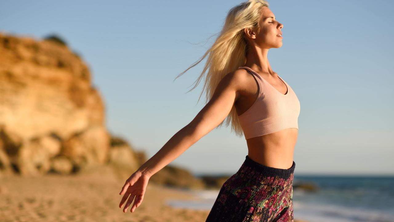 Ixmwdiotq69geuomxpql woman enjoying the sunset on a beautiful beach 7z6u3rm min