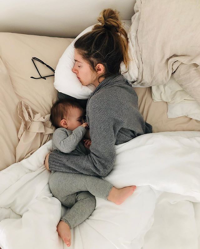 Mother laying in bed with her sleeping child
