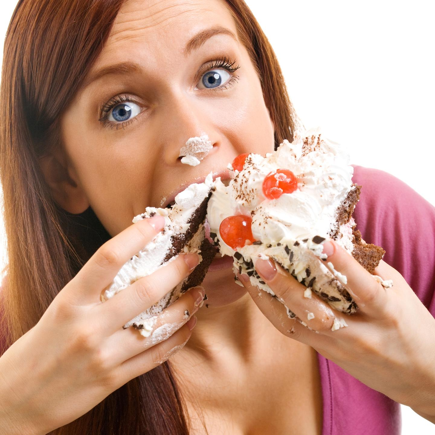 Woman stuffing cupcake in mouth