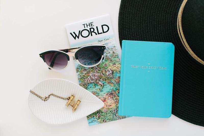 Sunglasses, a large brim hat, a passport holder, and a map of the world