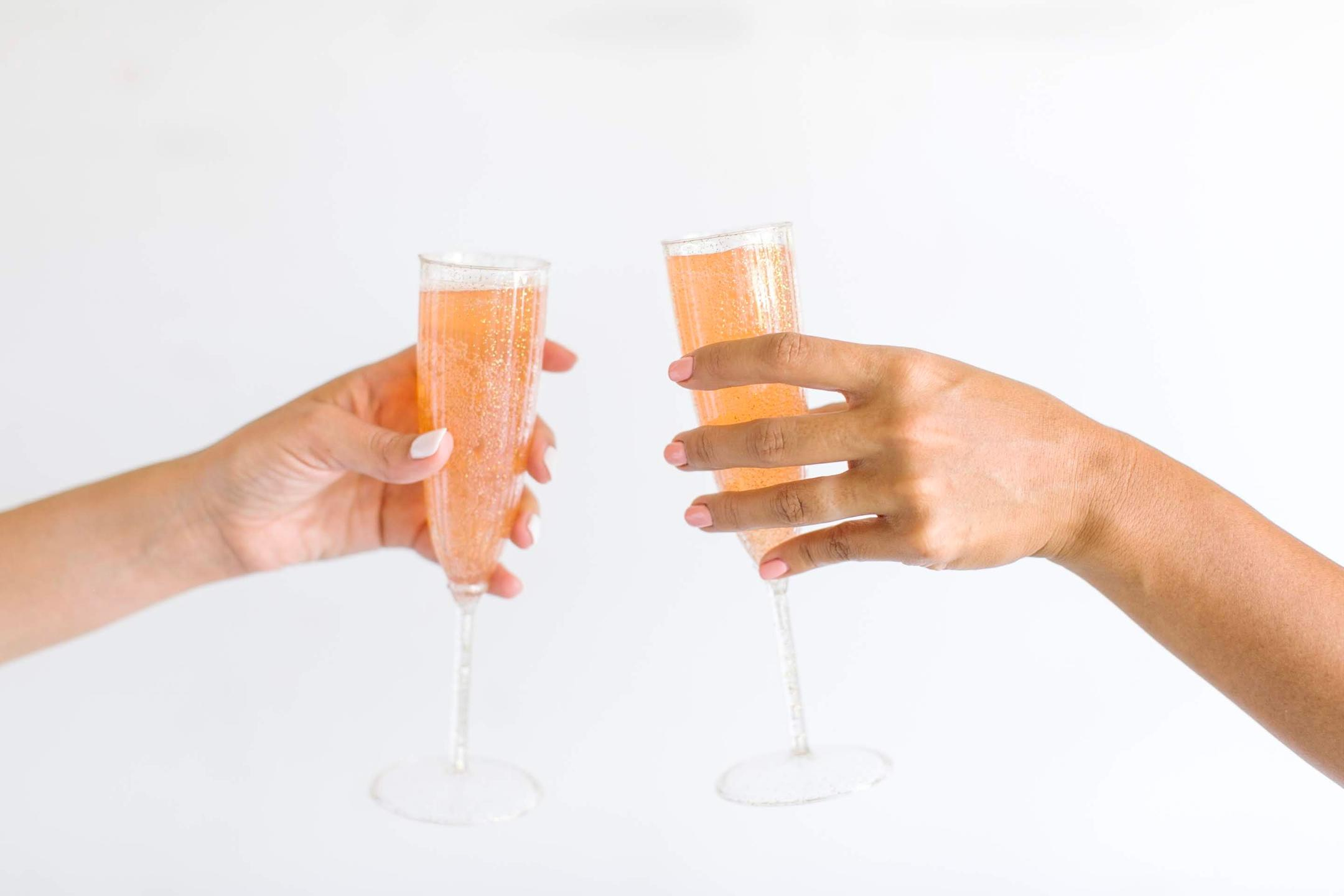 Two hands holding glasses of champagne about ready to cheers