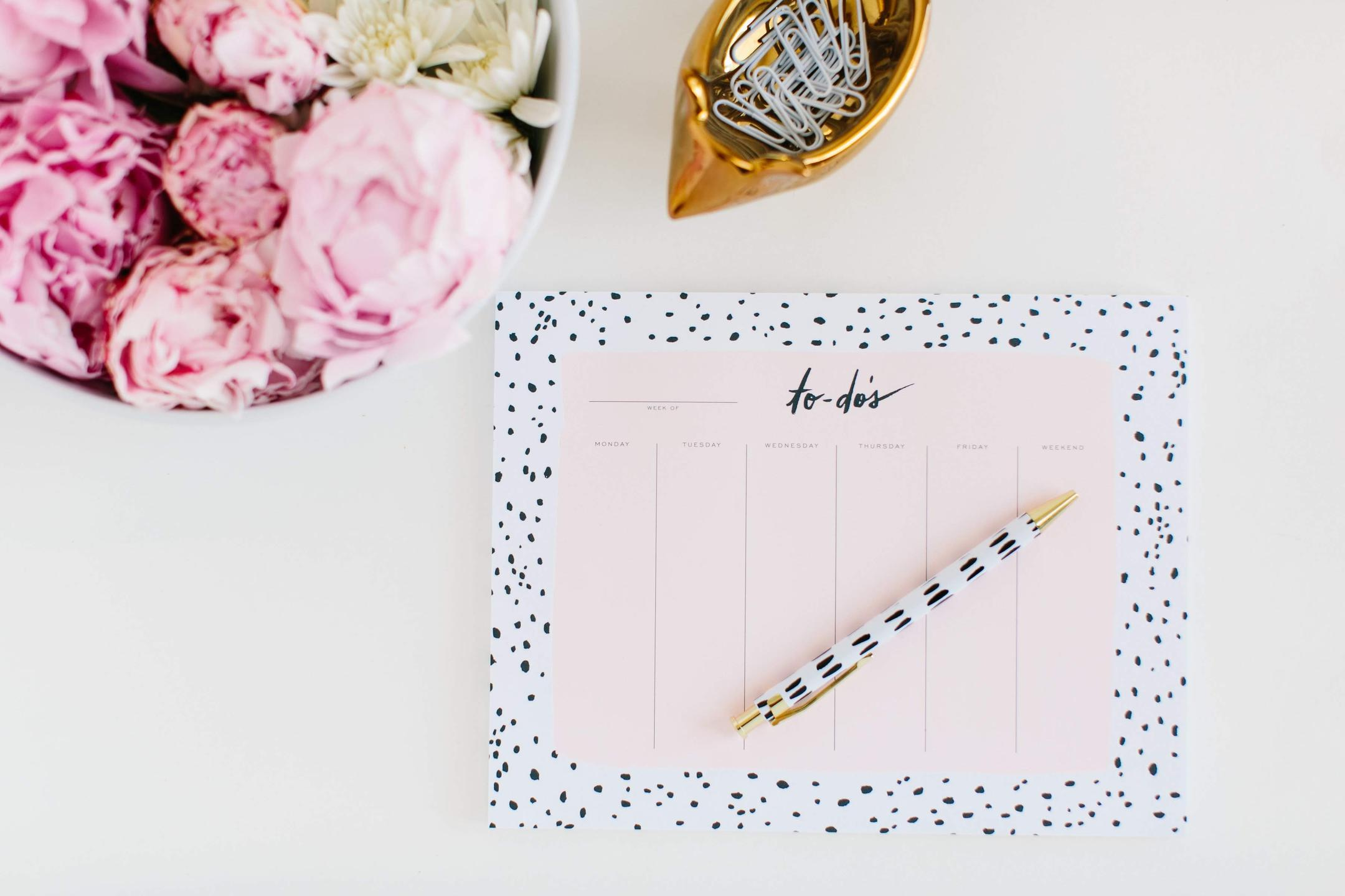 A cheerful to-do list with stylish pen surrounded by pink peonies and a gold mouse filled with paperclips