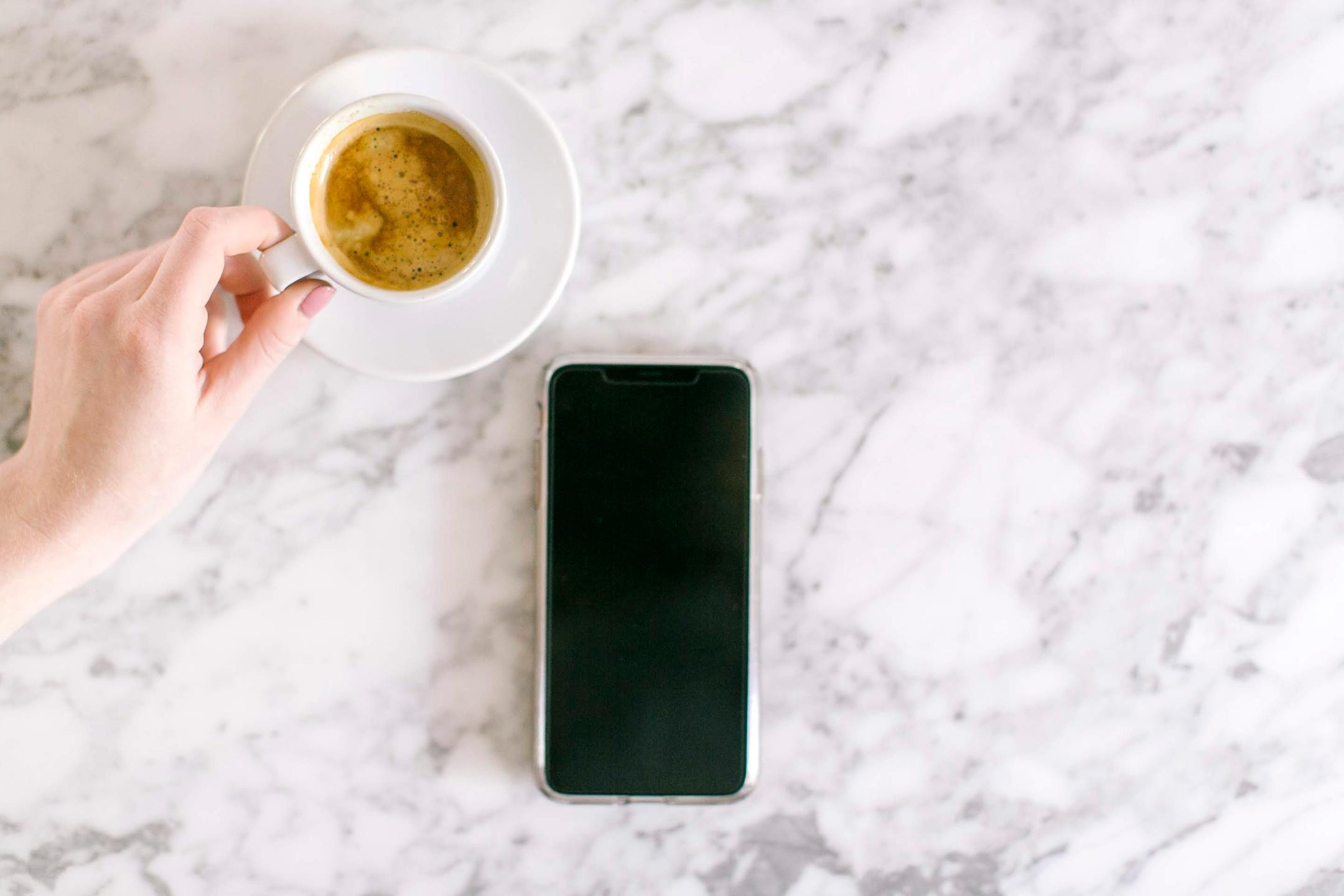 Cell phone and cup of coffee on marble countertop, hand reaching for coffee