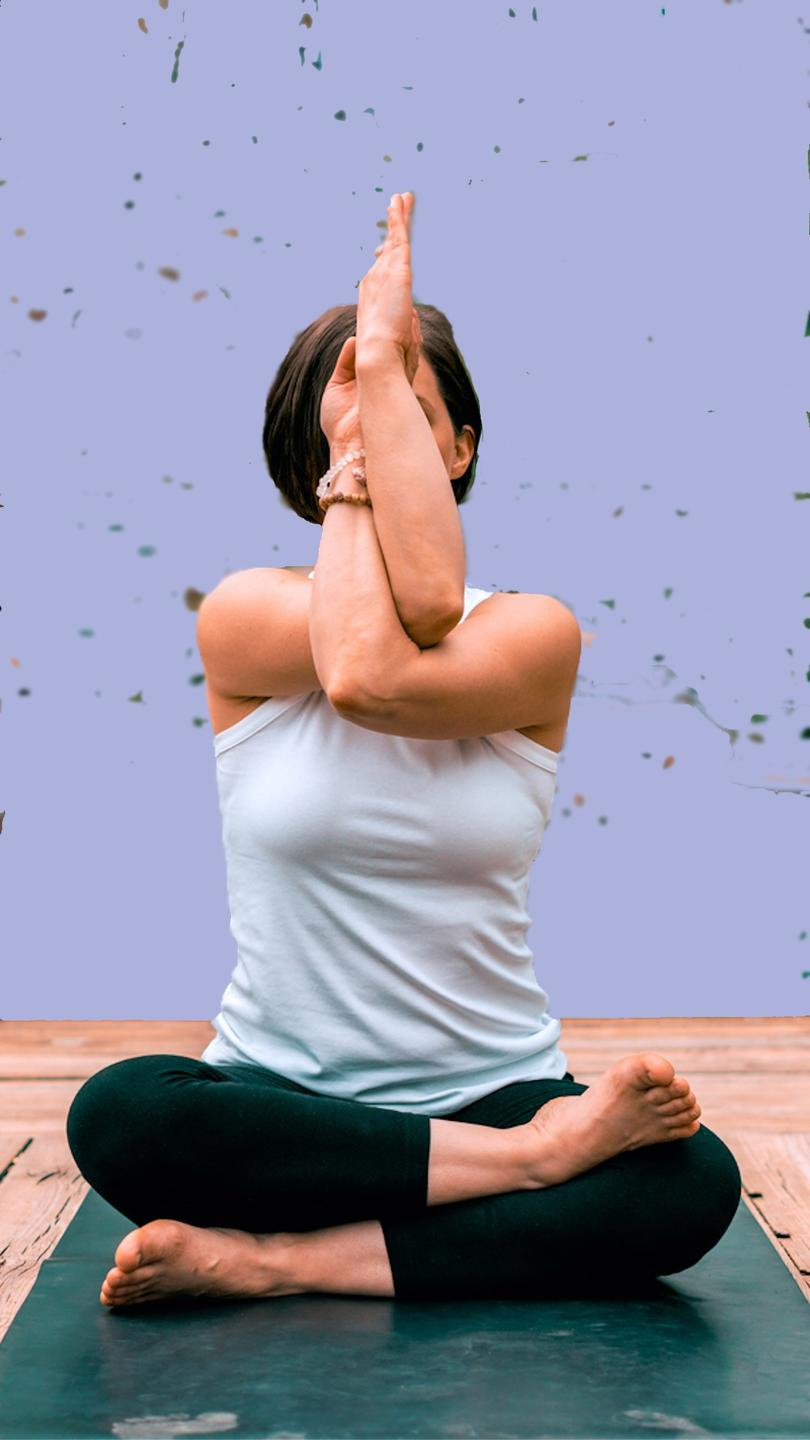 Seated lady doing a shoulder stretch in yoga