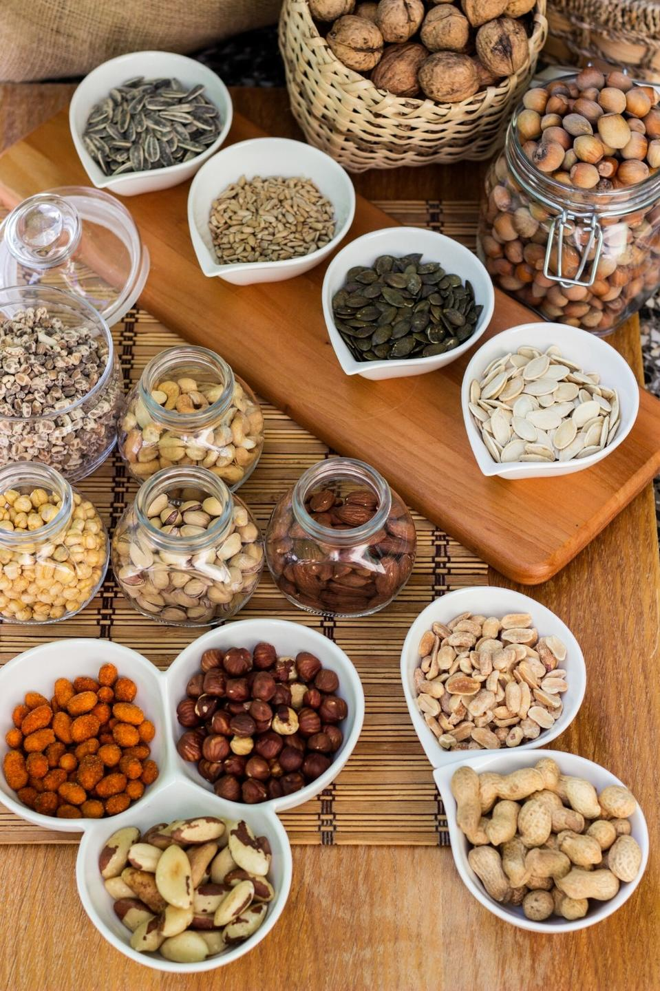 omega 3 sources, bowls of sunflower seeds, pumpkin seeds, hazelnuts, walnuts, pistachios, almonds and peanuts