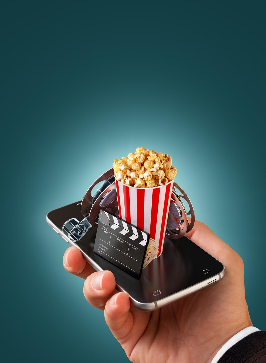 Phone in hand with online business entertainment items: movie tape, directors cut, popcorn
