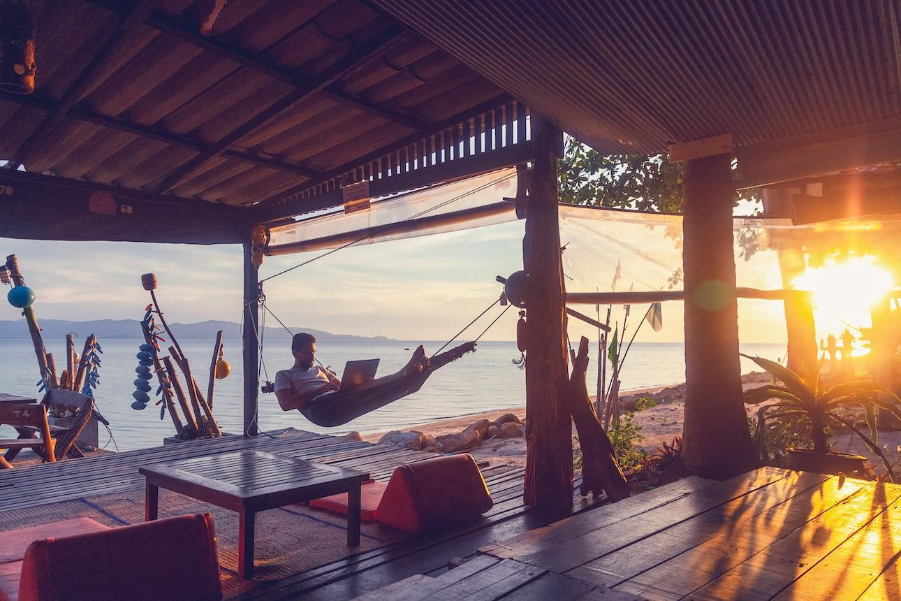 digital nomad in hammock on tropical beach