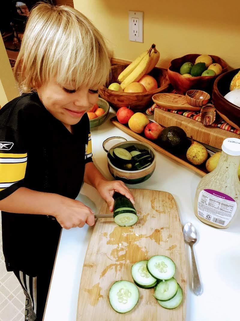 Your Vegan Family young boy cutting cucumbers