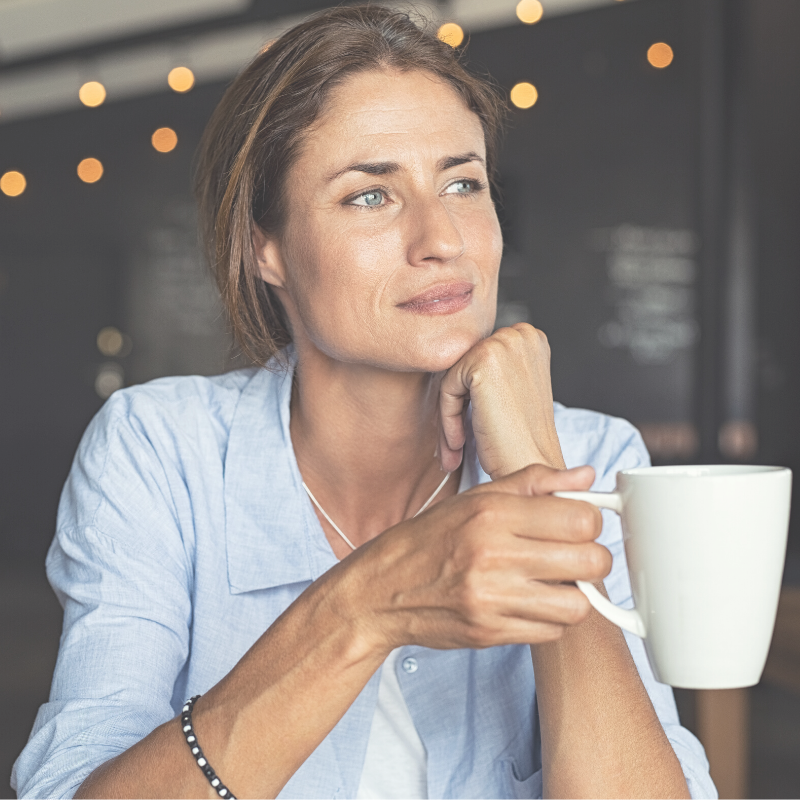 Beautiful woman over 40 holding a coffee.