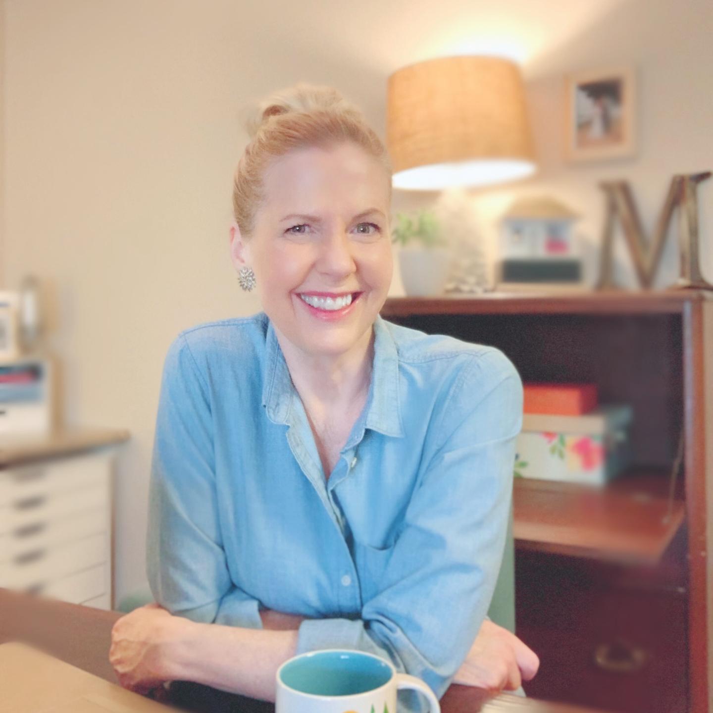Woman sitting at a desk smiling. Lori Massicot.