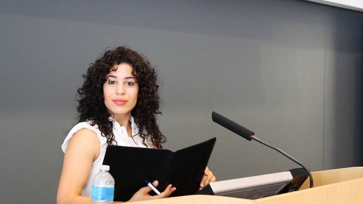 A confident younger woman with curly dark hair standing at a classroom podium holding her curriculum about to teach