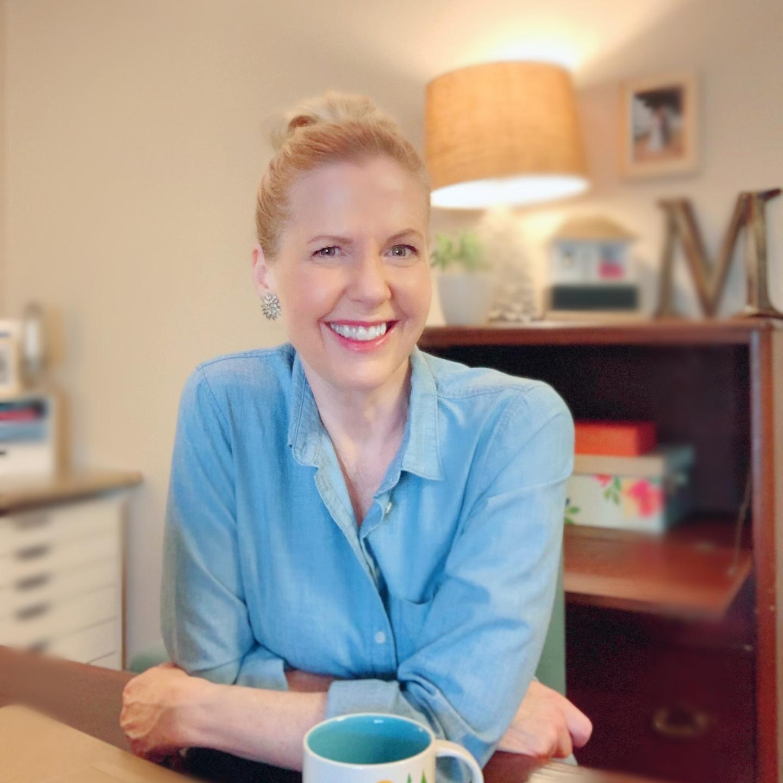 Lori Massicot sitting at a table smiling.
