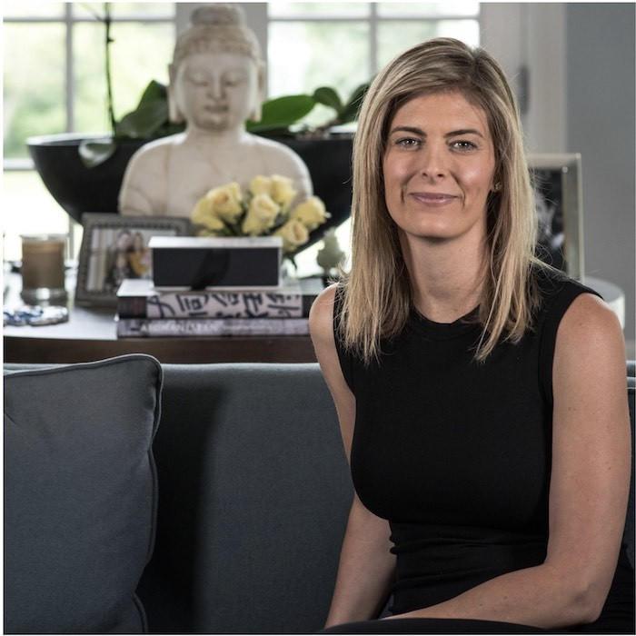 Megan Cooper wearing black top sitting on lounge at home