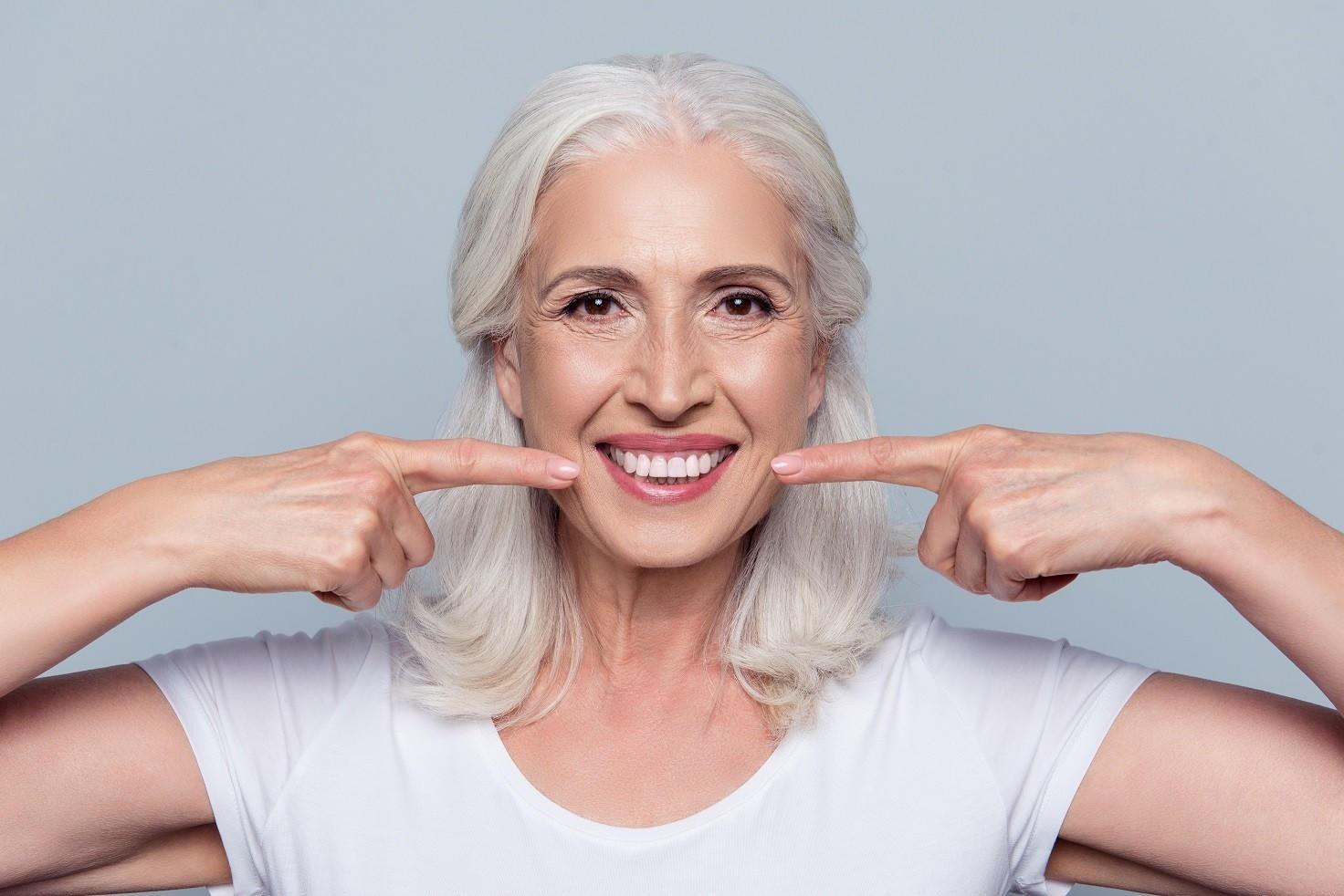 Frau lacht und zeigt auf Zähne