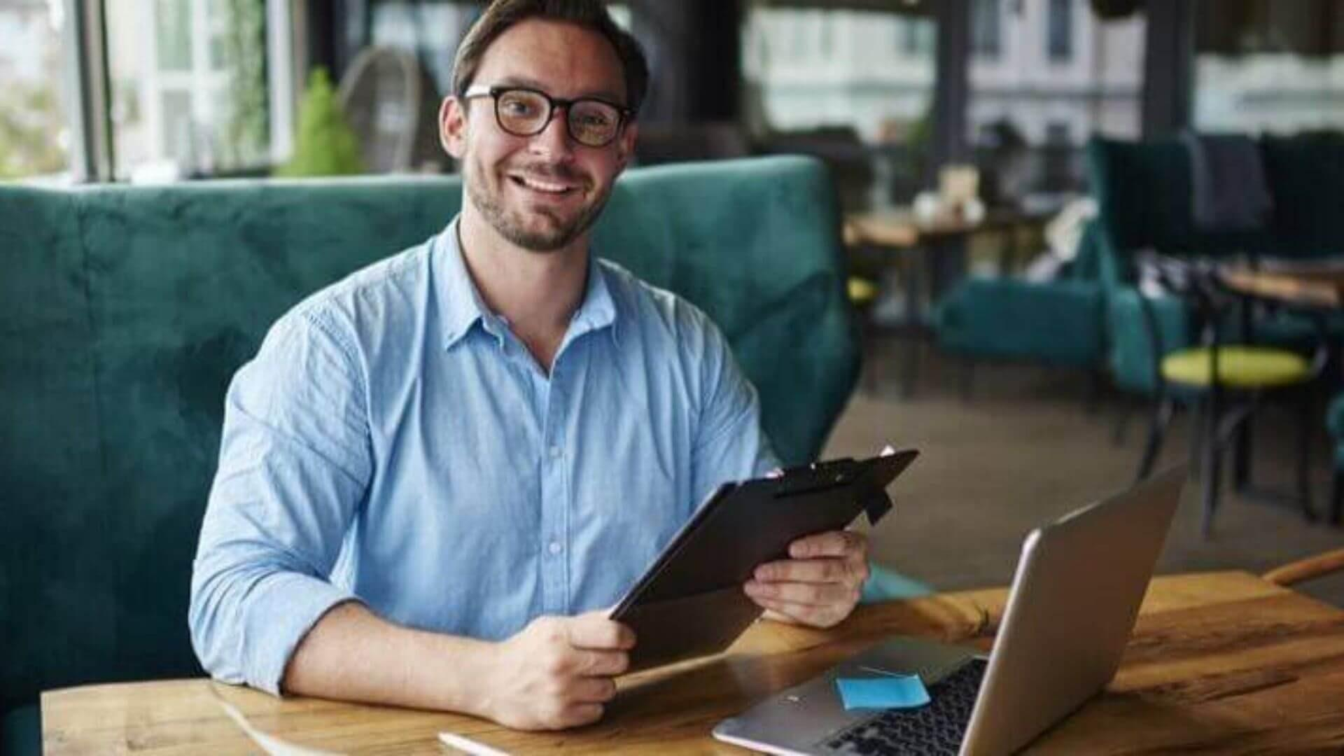 man holding ipad smiling at table
