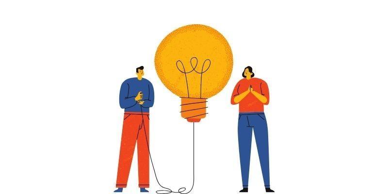 people standing around a lightbulb