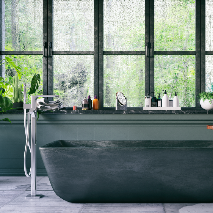 A charcoal granite bath tub with modern faucets.