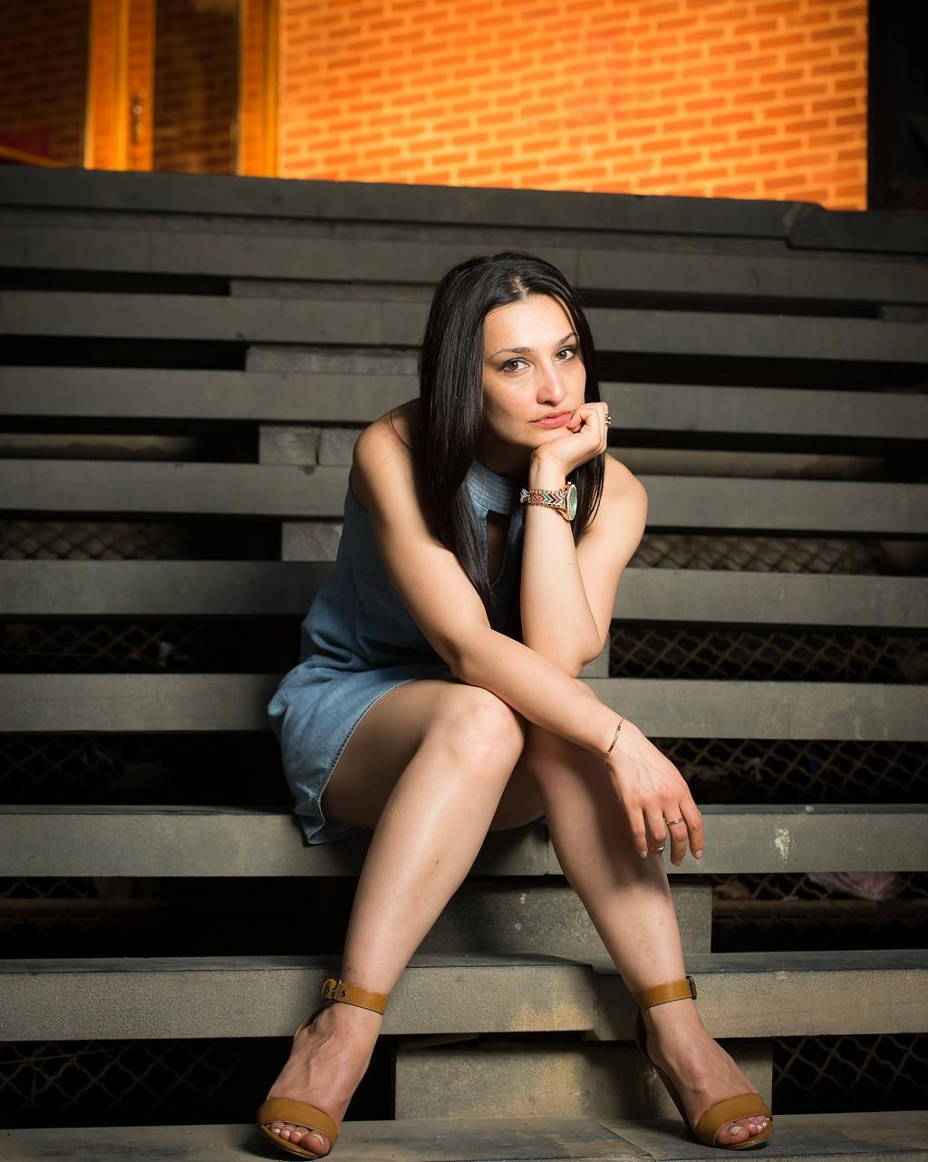 Anahit host of Viva La Flora Live Podcast seating on steps
