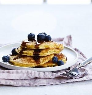 gluten free pancakes with blueberries on top and maple syrup stacked on a plate